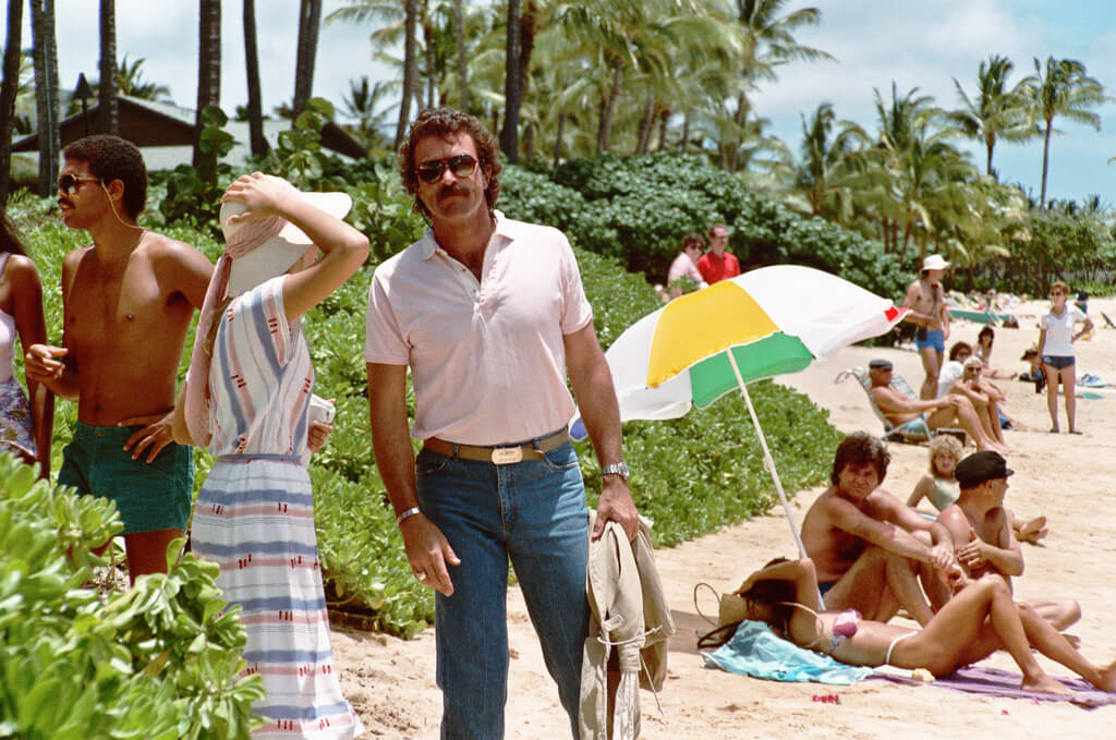 Tom Selleck stands on a beach.
